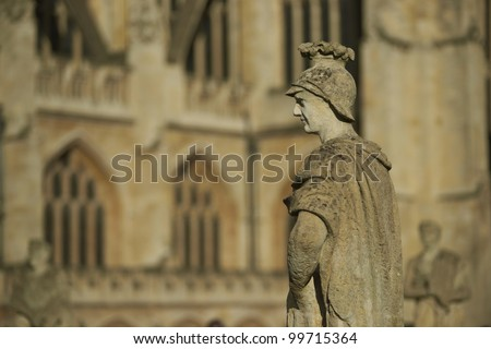Old weathered stone statue above the ancient Roman Baths in Bath, Somerset, England. Bath Abbey in the background.
