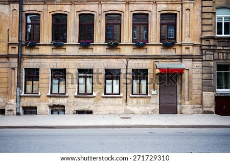 Old weathered street wall with some windows and door - stock photo