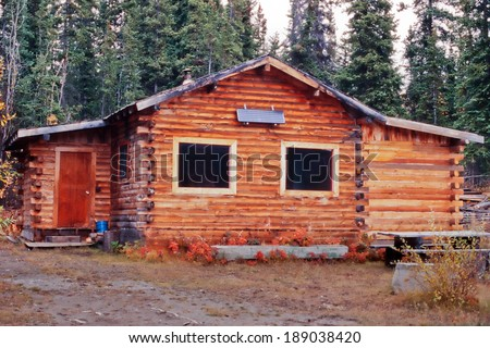 Old weathered traditional Yukon log cabin with exterior off-grid solar panel in the boreal forest taiga of Yukon Territory, Canada - stock photo