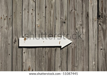 Old weathered wall or fence with white painted arrow sign and rusted nail heads showing - stock photo