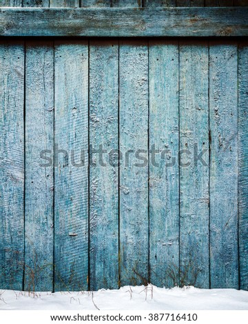 Old weathered wood plank fence and a ground covered with snow - stock photo