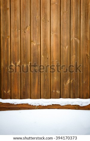 Old weathered wood plank fence and a ground covered with snow