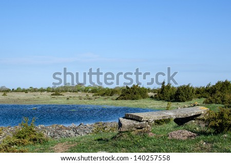 Old weathered wooden bench at a small pond. From the Great Alvar Plain at the island Oland in Sweden. - stock photo
