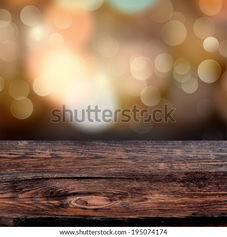 Old weathered wooden board with a sparkling bokeh of party lights in the background - stock photo