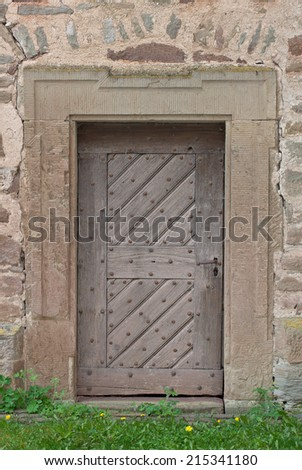 Old weathered wooden door with big, rusty nails in a stone portal  - stock photo
