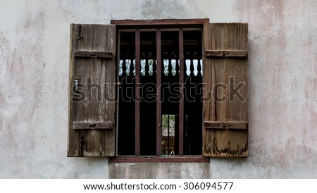 Old weathered wooden window with hinges