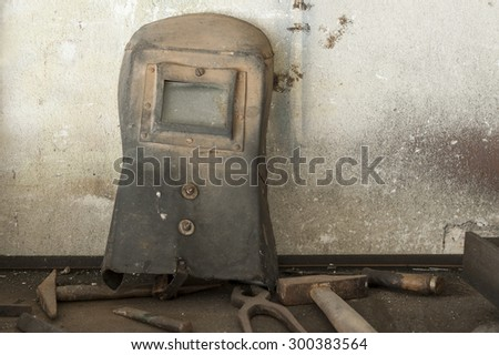 old welder's mask with old work tools in home garage - stock photo