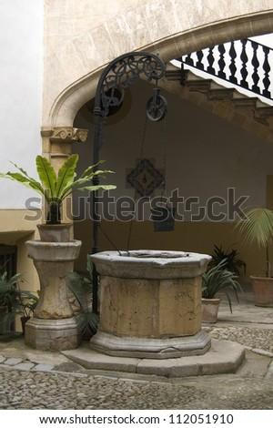 Old well in a courtyard of Palma de Majorca Balearic Islands - stock photo
