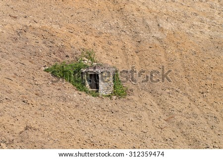 Old well made of stone almost covered by spontaneous vegetation  in a steep plowed field Piedmont Italy  - stock photo