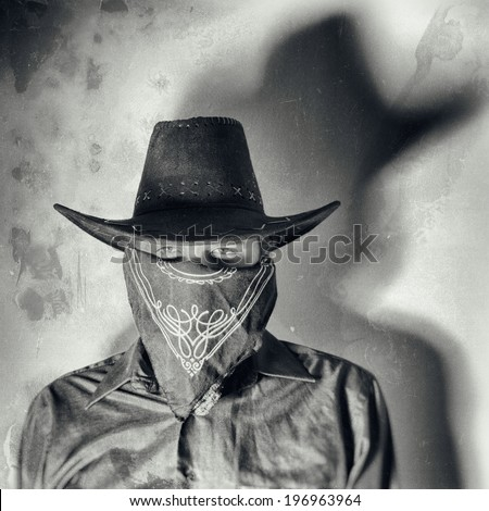 Old West Bandit. Old west bandit outlaw with covered face and cowboy hat, edited in vintage film style. - stock photo