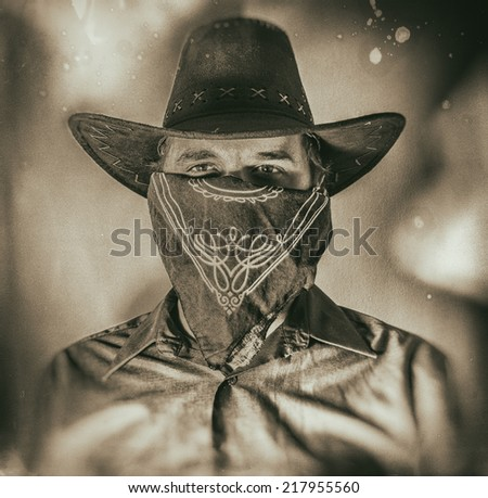 Old West Cowboy Bandit 2. Old west bandit outlaw with covered face and cowboy hat, edited in vintage film style. - stock photo