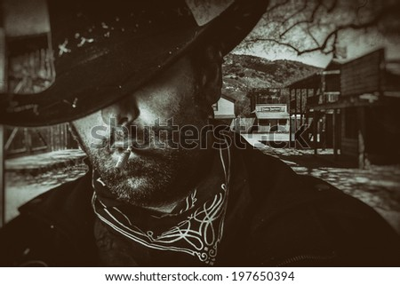 Old West Cowboy Western Town. An old west cowboy in a hat smoking a hand rolled cigarette with an old western town setting in the background, edited in vintage film style. - stock photo