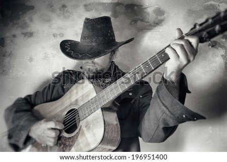 Old West Cowboy With Guitar. A cowboy playing a guitar, edited in vintage film style. - stock photo