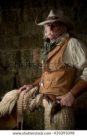 Old west cowboy with woolie chaps, pistols, vest and cowboy hat - stock photo