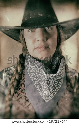 Old West Cowgirl Eyes. Old west cowgirl looks into camera, edited in vintage film style. - stock photo