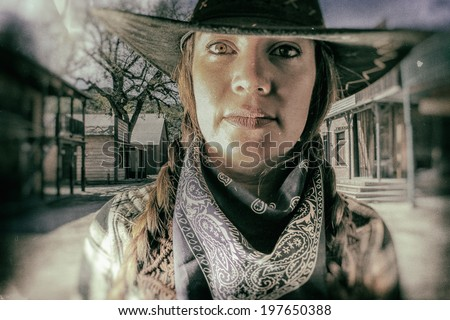 Old West Cowgirl Eyes Western Town. Old west cowgirl looks into camera with western town setting in background, edited in vintage film style. - stock photo