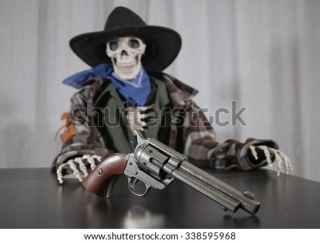 Old West Revolver Skeleton. Old west bandit outlaw skeleton at a poker table with a colt 45 pistol revolver, edited in vintage film style with shallow depth of field. - stock photo