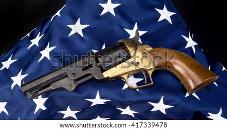 Old west six shooter gun  on American flag. - stock photo
