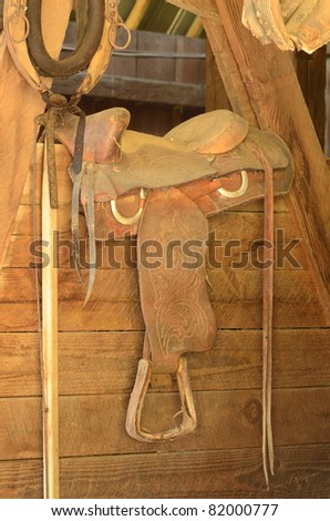 Old western saddle in a horse barn - stock photo