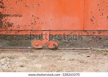 Old wheel of metal slide door - stock photo