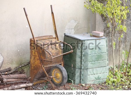 old wheelbarrow in the garden and the big green container for compost to be used as natural fertilizer for the garden ecology - stock photo
