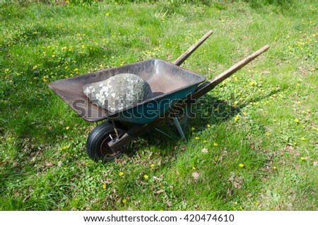 Old wheelbarrow loaded with a big stone in a garden at spring - stock photo