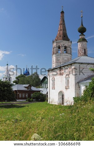 old white church and small wooden houses on the green hill in Rassian town Suzdal - stock photo