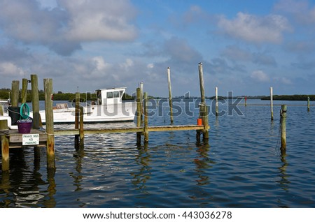 Old White Fishing Boat and Dock on a Bay in Florida   - stock photo