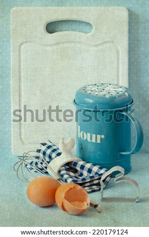 Old white kitchen cutting board with copy-space for writing menu, flour strainer, napkin and napkin ring, whisk and eggs. Toned photo. Vintage style. - stock photo
