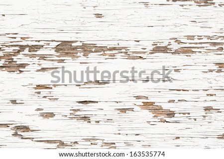 Old white paint flaking off a wooden surface. - stock photo