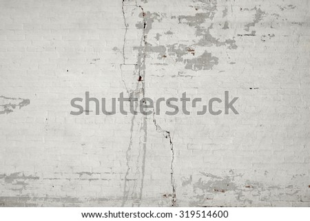 Old White Painted Cracked Brick Wall With Peeled Layers Background Texture - stock photo