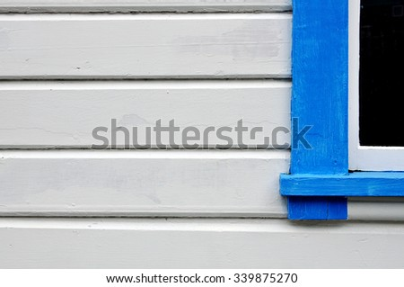 old white painted exterior with blue window - stock photo