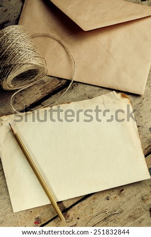 Old white sheet of paper and a pencil on a wooden background.The envelope and the coil of twine.