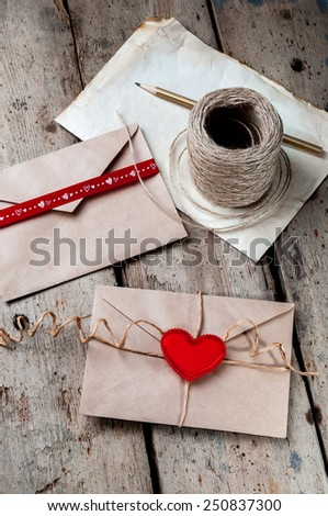 Old white sheet of paper and a pencil on a wooden background.The envelope,coil of twine and  little red hearts. - stock photo