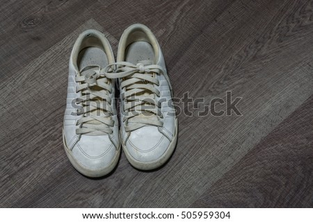 Old white shoes on the wood floor with high contrast