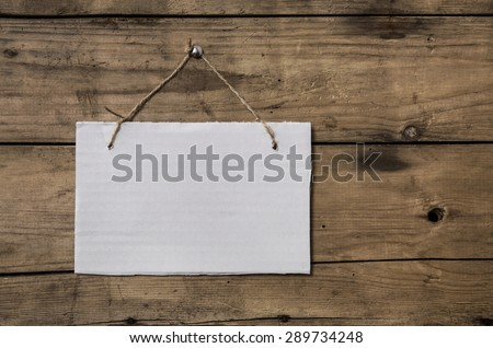 Old white sign hanging on a wooden wall. - stock photo