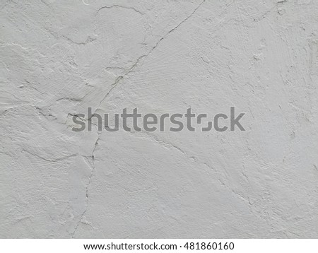Old white wall with cracked paint for background.