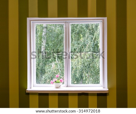 Old white wood window in striped brown and yellow wall