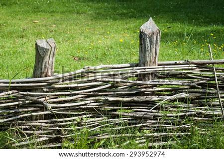 Old wicker fence in a field - stock photo