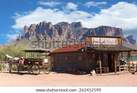 Old Wild West Cowboy town with horse drawn carriage and mountains in background - stock photo