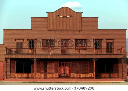 Old Wild West desert cowboy town with cactus and saloon - stock photo
