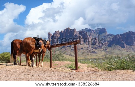 Old Wild West in the desert with mountains and horses - stock photo