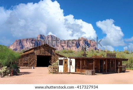 Old Wild West town with mountains range in background - stock photo