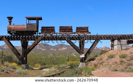 Old Wild West train with mining carts passing over an old wooden bridge with mountains, cactus and wild flowers in background - stock photo