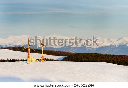 Old wind turbines with Carpathian Mountains in the background. - stock photo