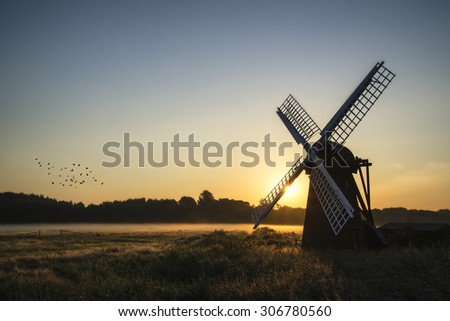 Old windmill in foggy English countryside landscape  - stock photo