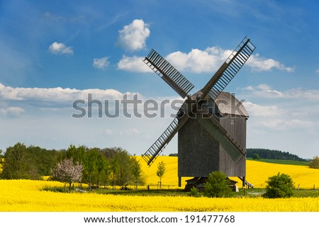 Old windmill in West Pomerania near Storkow, Germany, surrounded by rape fields in spring - stock photo