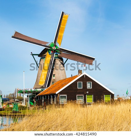 Old windmill in Zaanse Schans, traditional village in Netherlands, North Holland, high grass, blue cloudy sky - stock photo