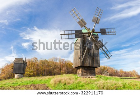Old windmill on a background of forest and sky with blurred clouds in autumn day. National Museum of Ukrainian Architecture and Culture, Kiev, Ukraine..   - stock photo