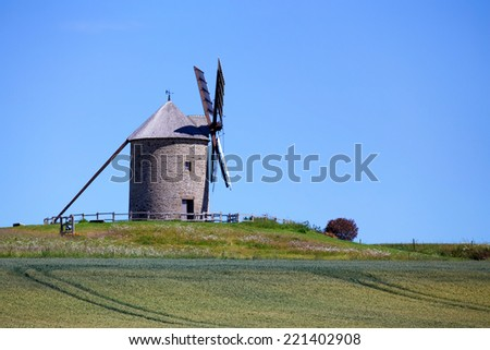 Old windmill on picturesque meadow in Europe rustic landscape - stock photo